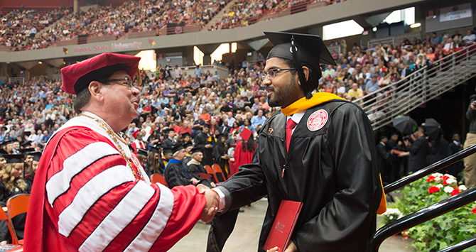 Student shaking President Dietz hand at graduatiion.